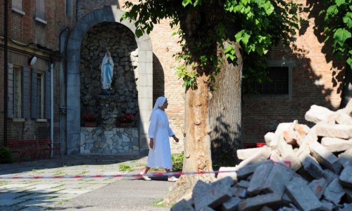 A nun walks past rubble in Mirandola after an earthquake on May 29. (OLIVIER MORIN/AFP/GettyImages)