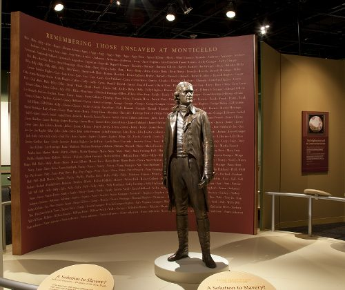"A statue of Thomas Jefferson, standing in front of a wall containing the names of the more than 600 enslaved people he owned, greets visitors to the exhibition ""Slavery at Jefferson's Monticello: Paradox of Liberty."" (Michael Barnes/Smithsonian Institution)"