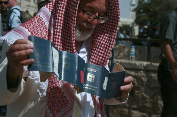 An old man displays a series of old passports after passing through a security gate at the Damascus Gate to the Old City of Jerusalem. (Genevieve Long/The Epoch Times)
