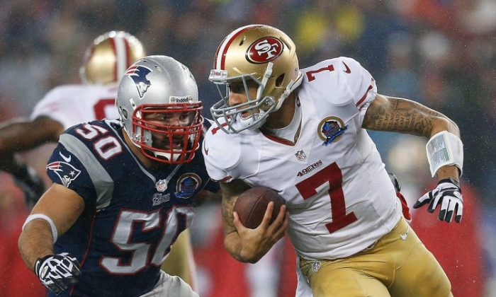 Colin Kaepernick (R) of the San Francisco 49ers evades Rob Ninkovich of the New England Patriots on Sunday, Dec. 16, 2012 at Gillette Stadium in Foxborough, Mass. (Jim Rogash/Getty Images)