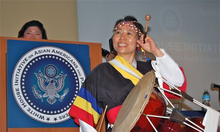 A Korean drummer closes the first White House Regional Summit on Asian Americans as Tricia Sung looks on. (Mary Silver/The Epoch Times)