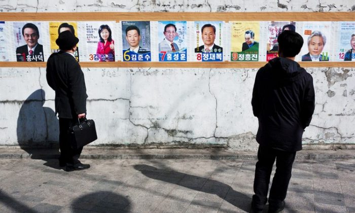 South Korean voters view promotional posters of candidates for the General Assembly election on April 11. (Jarrod Hall/The Epoch Times)
