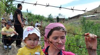 An ethnic Uzbek mother holds her daughter as they wait at the Kyrgyz-Uzbek border outside a village of Suratash on June 14, 2010. (Viktor Drachev/AFP/Getty Images)