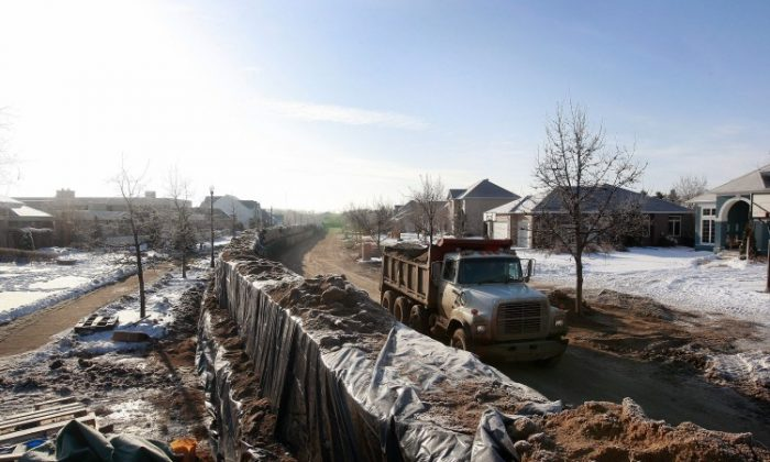 """A levee holds back flood water from the Red River, N.D. U.S. Levees and waterways form a """"hidden backbone"""" of the U.S. freight network and yet age and deterioration are causing significant delays and affecting commerce according to a new report on U.S. infrastructure. (Scott Olson/Getty Images)"""