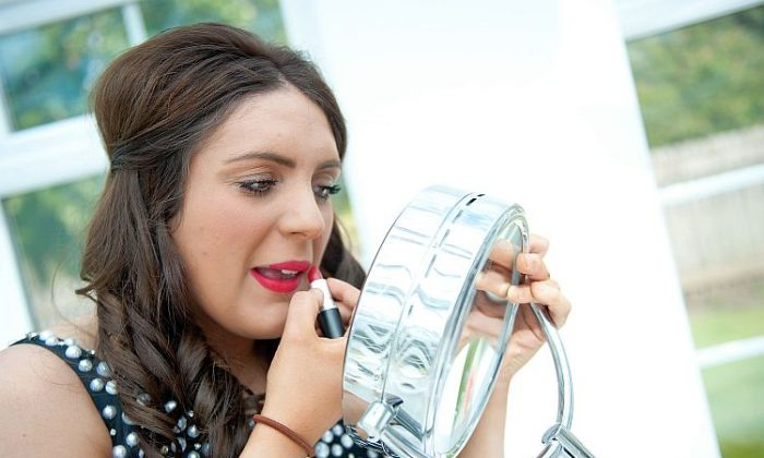 A young woman applies lipstick before a school prom in this file photo. The FDA recently tested 400 lip colors of lipstick for traces of lead. Despite finding traces in lipstick, the agency said it was not a safety concern. (Bethany Clarke/Getty Images)