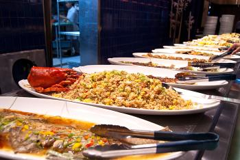 A fresh plat of lobster rice is nestled between cooked sea bass and other dishes on the buffet table of Ichi Umi. (Joshua Philipp/The Epoch Times)
