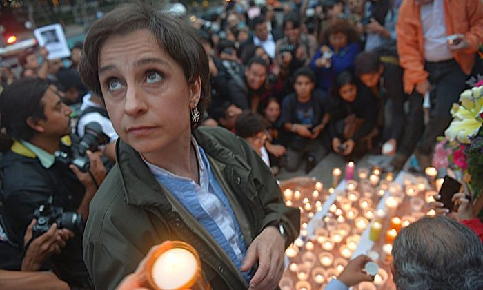 People mourn murdered Mexican journalists by placing candles and pictures at the Independence Angel monument in Mexico City on May 5. (Yuri Cortez/AFP/GettyImages)