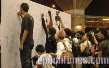 Fans write messages on the white board for Michael Jackson. (The Epoch Times)