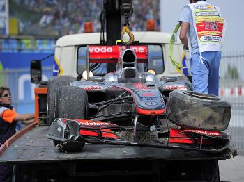 The broken McLaren of Lewis Hamilton is towed back to the garages. (Josep Lago/AFP/Getty Images)