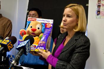 NYPIRG consumer attorney Tracy Shelton holds the 'Love to Play Puppy' from Fischer Price, which was found to contain high levels of bromine and low levels of mercury. The toy is marketed for babies.  (Joshua Philipp/The Epoch Times)