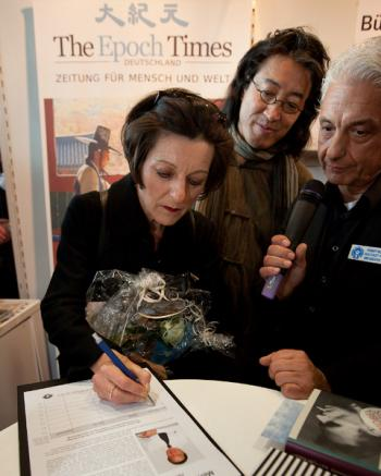Nobel Herta Muller signs a petition to free human rights attorney Gao Zhisheng at the Epoch Times display during the Frankfurt Book Fair. (Jason Wang/The Epoch Times)