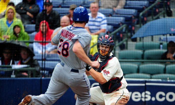 Daniel Murphy (L), who had two hits against the Braves, was tagged out by Atlanta catcher David Ross (R) at home in the fifth inning. (Scott Cunningham/Getty Images)
