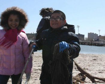 TAKING OUT THE TRASH: Jose Quizhpe, 6, picks up litter at Kaiser Park in Brooklyn on Saturday.  (Tara MacIsaac/The Epoch Times)