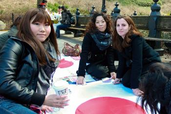 HAND-IN-HAND: Volunteers for the Hand-in-Hand Project for Japan collect funds for earthquake relief, and offer New Yorkers strolling through Central Park a chance to sign a Japanese flag with a message of hope to be sent to the devastated region. (Tara MacIsaac/The Epoch Times)