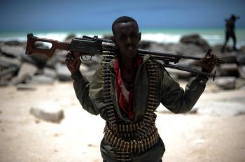 SOMALI SECURITY: A militia man stands on a beach near the town of Hobyo, Central Somalia, on Aug. 20. The fledging Galmadug administration in Central Somalia says it lacks the resources to confront the well-organized and well-equipped pirate gangs.  (Roberto Schmidt/Getty Images )