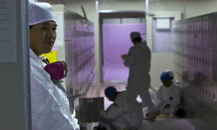 Japanese workers wearing protective suits gather near their lockers inside the emergency operation center at the Fukushima Daiichi nuclear power station in Okuma on Nov. 12, 2011. (David Guttenfelder/AFP/Getty Images)