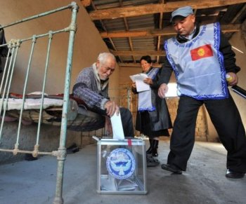 A Kyrgyz man sitting on his bed casts his vote in the village of Kyzyl-Birlik, Kyrgyzstan.  (Vyacheslav Oseledko/AFP/Getty Images)