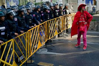 RED SHIRT COWBOY: A red-shirt protester stands in front of Thai riot police near Ratchaprasong intersection in Bangkok on Jan. 9. Red shirt paraphernalia of all kinds was for sale at the 2011's first anti-government rally.  (Nicolas Asfouri/Getty Images)
