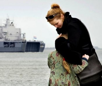 UNCERTAINTY: A young girl is comforted by her mother as the Dutch marine vessel Hr.Ms. Johan de Witt where her father is serving, leaves from the harbor of Den Helder on April 5. The ship has been sent to patrol as part of the E.U. counterpiracy mission off the coast of Somalia. (Robin Van Longkhuijsen/Getty Images )