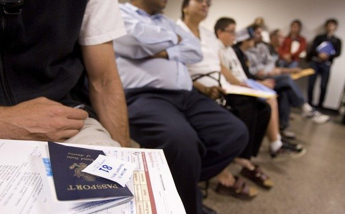 People wait to get their passport applications submitted at the United States passport agency office in San Francisco in this file photo. Two U.S. senators have sponsored a bill to allow foreigners who purchase real estate in the United States to extend their visa stay. (David Paul Morris/Getty Images)