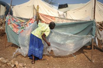 A Haitian woman sets up her makeshift tent at a camp in Port-au-Prince on March 1. (Eitan Abramovich/AFP/Getty Images)