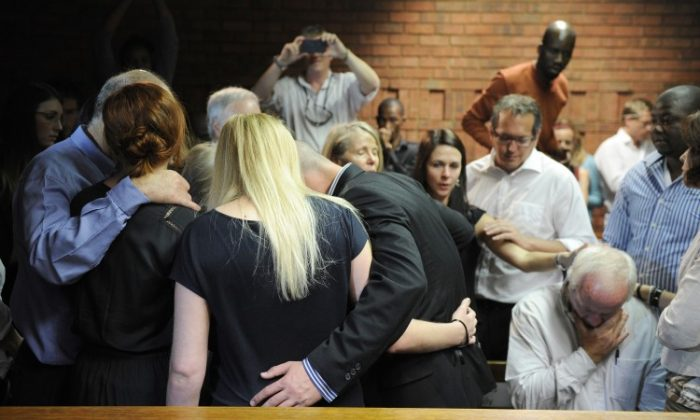 The father and other family members of Oscar Pistorius, South African Olympic sprinter who is set to be charged with murdering Reeva Steenkamp, comfort each other on February 19, 2013 after the athlete's bail hearing was adjourned at the Magistrate Court in Pretoria. (Stephane De Sakutin/AFP/Getty Images)
