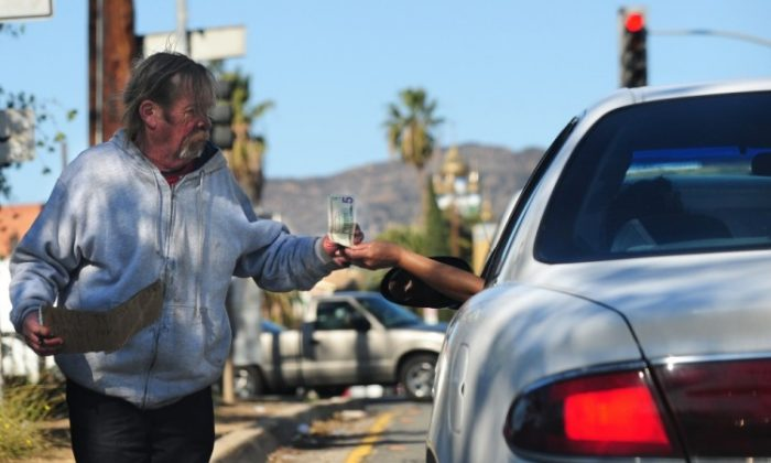 """A man holding an unfinished note which reads """"Like to see my family for ..."""" receives some money from the driver of a vehicle stopped at a red light in Hollywood, Calif., last month. A recent Indiana State University report shows that as the middle class has shrunk, poverty has risen by 27 percent since 2006. (Frederic J. Brown/AFP/Getty Images)"""