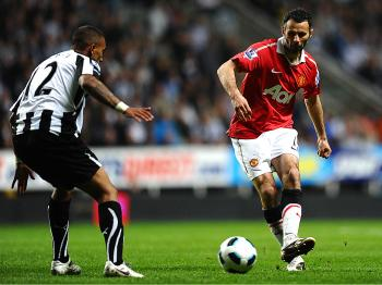 Manchester United's Welsh midfielder Ryan Giggs (R) shoots past Newcastle United's English defender Danny Simpson during the English Premier League football match between Newcastle United and Manchester United at St James' Park. (Paul Ellis/AFP/Getty Images)