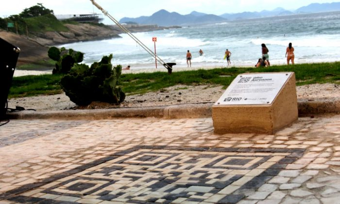 A man tests the QR code at Arpoador Beach, Rio de Janeiro, Brazil, on Jan. 25. It is the first of 30 codes that will appear at tourist attractions in Rio in preparation for hosting the 2016 Olympics. (Bruno Menezes/The Epoch Times)