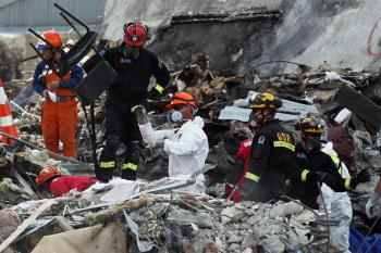 Rescue workers clear out remains from the CTV building on March 1, 2011 in Christchurch, New Zealand. The quake, which was an aftershock of a 7.1 magnitude quake that struck the South Island city on September 4, 2010, has seen damage and fatalities far exceeding those of the original. (Hannah Johnston/Getty Images)