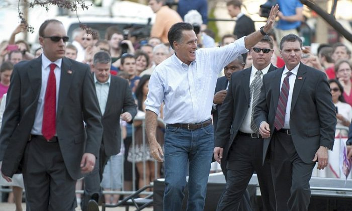 GOP presidential candidate Mitt Romney waves to supporters March 19 at Bradley University in Peoria, Ill. In the lead up to Tuesday's Illinois primary, Romney is ahead of Santorum by eight points, according to RealClearPolitics.com (Don Emmert/AFP/Getty Images)