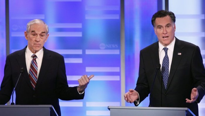 Republican presidential candidate Rep. Ron Paul (R-Tex) (L) gestures towards fellow candidate and former Massachusetts Gov. Mitt Romney in the ABC News, Yahoo! News, and WMUR Republican Presidential Debate at Saint Anselm College in Manchester, N.H., Jan. 7. The GOP contenders are in the final stretch of campaigning for the New Hampshire primary, to be held Tuesday Jan. 10. (Win McNamee/Getty Images)