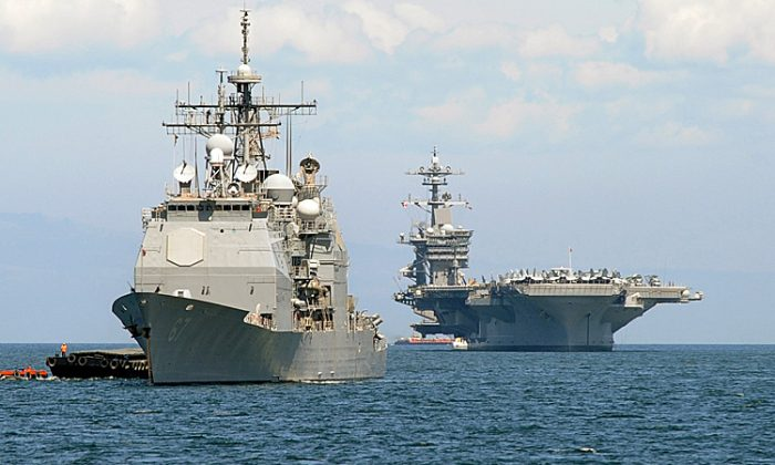 The U.S. aircraft carrier Carl Vinson (R) and the cruiser USS Bunker Hill (L) sit anchored off Manila Bay after arriving on May 15, 2011 for a four-day port of call accompanied by three other warships. U.S. carrier groups allow it to project military power in the Asia-Pacific, balancing the rising power of China, in line with a new U.S. strategic focus on the region. (Jay Directo/AFP/Getty Images)