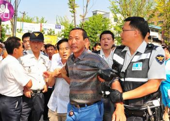Police arrest a man attacking participants in the 'Quit the CCP' parade held in Ansan City, South Korea, on Sept. 13, 2009. (Jin Guohuan/The Epoch Times)
