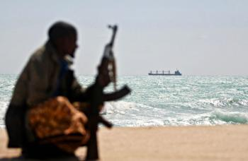 An armed Somali pirate along the coastline while the Greek cargo ship, MV Filitsa, is seen anchored just off the shores of Hobyo town in Northeastern Somalia where its being held by pirates.  (Mohamed Dahir/AFP/Getty Images)