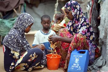 A woman who fled the recent fighting in Mogadishu prepares breakfast next to a makeshift hut at internally displaced camp on the outskirts of Mogadishu. (Mohamed Dahir/AFP/Getty Images)