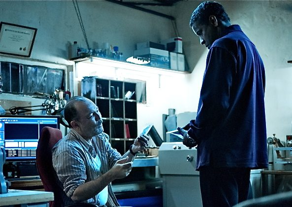 "Ruben Blades prepares documents for Denzel Washington (R) in the action-thriller ""Safe House,"" a film about a young CIA agent on the run with his charge. (Universal Pictures)"