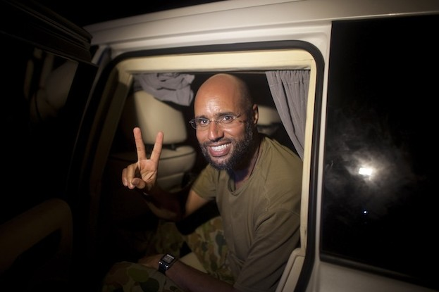 Saif al-Islam Kadhafi, son of former Libyan leader Moammar Gadhafi, flashes the V-sign for victory as he appears in front of supporters and journalists in the Libyan capital Tripoli in the early hours of August 23, 2011. (Dario Lopez-Mills/AFP/Getty Images)