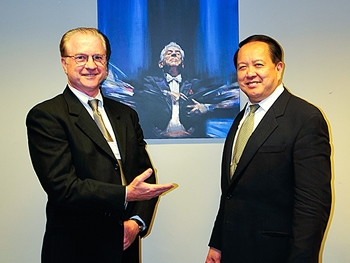 (L-R) George Stamm and Mr. Ling stand in front of a picture of the conductor's beloved mentor, Leonard Berstein. (Xusheng Li/Epoch Times)