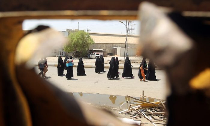 Iraqi Shiite pilgrims heading to Kadhimiya walk past the site of a roadside bomb in Baghdad's Karrada district on June 13, as a wave of bombings and shootings rocked Iraq during a major Shiite religious commemoration, killing scores of people and wounding dozens more. (Ahmad Al-Rubaye/AFP/GettyImages)