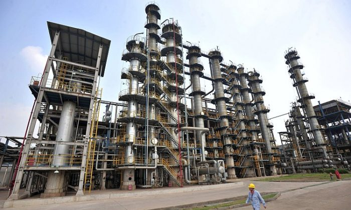 A Chinese worker walks by a Sinopec oil refinery in Hubei Province, May 2011. In a deal announced Jan. 3, China's Sinopec is paying $2.2 billion for a stake in Oklahoma-based Devon Energy Corp. (STR/AFP/Getty Images)