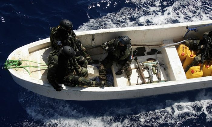 French soldiers sit alongside a cache of weapons seized from suspected Somali pirates as they arrive by launch at the French warship 'Le Nivose' on May 3, 2009, as part of EU's Atalante anti-piracy naval mission. (Pierre Verdy/AFP/Getty Images)