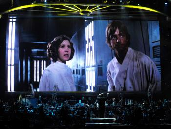 Actress Carrie Fisher's Princess Leia Organa character and actor Mark Hamill's Luke Skywalker character from 'Star Wars Episode IV: A New Hope' are shown on screen while musicians perform during 'Star Wars: In Concert' at the Orleans Arena in Las Vegas. (Ethan Miller/Getty Images)