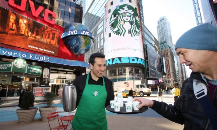 A barista joins the morning rush-hour crowd to distribute samples of the new Starbucks Tribute Blend™ outside a store in New York's Times Square, one of only four stores globally showcasing the new logo in celebration of Starbucks 40th anniversary. (Courtesy of Starbucks Corporation)