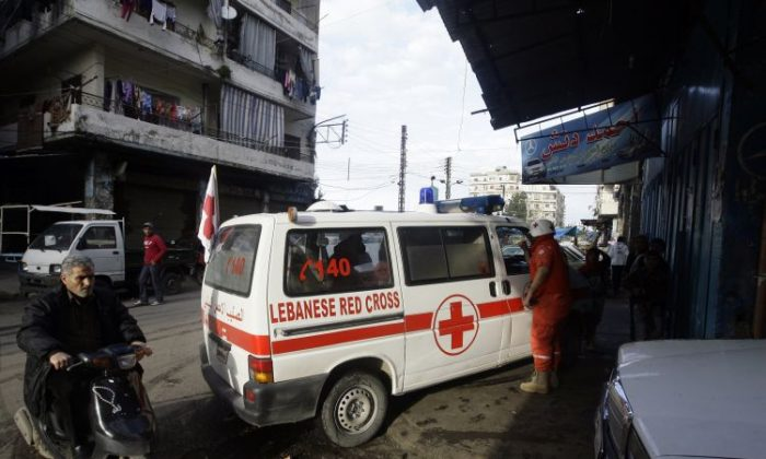 Red Cross volunteers arrive to evacuate wounded people in the Sunni neighbourhood of Bab al-Tabbaneh, on Feb. 11, 2012. The Red Cross on Sunday said that it still cannot get into the Homs neighborhood of Baba Amr, which has been under attack by the Syrian army. (Joseph Eid/AFP/Getty Images)