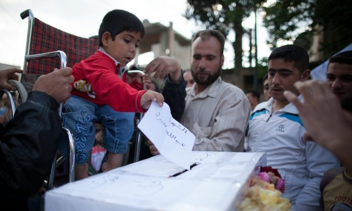 A handicapped Syrian boy casts a paper bearing the name of a 'martyr' into a coffin-like symbolic ballot box during an anti-election demonstration in the city Qusayr, Syria, on May 7. (STR/AFP/GettyImages)