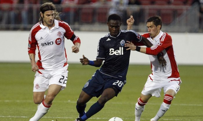 Toronto FC's Torsten Frings (L) and Eric Avila (R) put some heat on Vancouver Whitecaps Gershon Koffie at BMO Field in Toronto Wednesday night. Toronto defeated Vancouver 1-0 to win the Voyageurs Cup for the fourth straight year and a place in CONCACAF Champions League. (Abelimages/Getty Images)