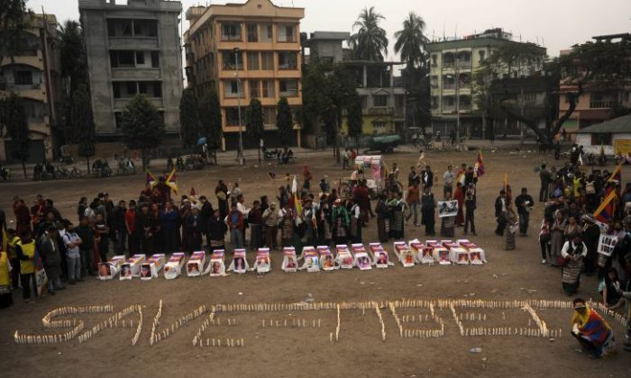 Tibetans offer prayers near mock coffins to represent self-immolated monks with candles forming 'Save Tibet' during a rally in Siliguri on February 8. (Diptendu Dutta/AFP/Getty Images)