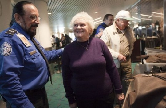 Transportation Security Administration (TSA) officer Stephen Candia (L) explains new rules to Evelyn Schulze, 76, at a security check at Portland International Airport (PDX) March 19 in Portland, Ore. The TSA has modified screening procedures for passengers 75 and older, allowing them to keep their shoes on during screening. The change has been implemented at four airports nationwide as a part of a pilot program. (Natalie Behring/Getty Images)