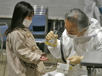 RADIATION SCAN: A young girl submits her hands for a radiation scan at a screening center in Koriyama in Fukushima prefecture March 22. An expert from the Institute for Science and International Security said the Japanese government waited too long to raise the classification of the country's nuclear crisis to 7, the highest level possible, undermining the purpose of the classification.  (Go Takayama/Getty Images)